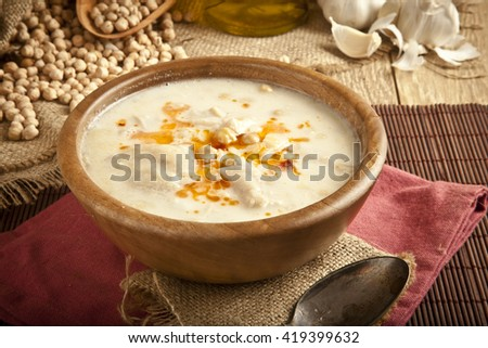 Turkish traditional tripe soup on rustic background with wooden table - stock photo