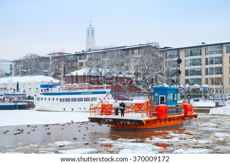 Turku, Finland - January 17, 2016: Ordinary passengers on historic city boat Fori, light traffic ferry that has served the Aura River for over a hundred years, first taking passengers in 1904