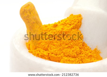 Turmeric barks, powder in white granite pestle and mortar isolated on white background