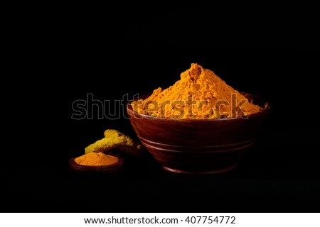 Turmeric powder and roots or sticks in wooden bowl on black background - stock photo