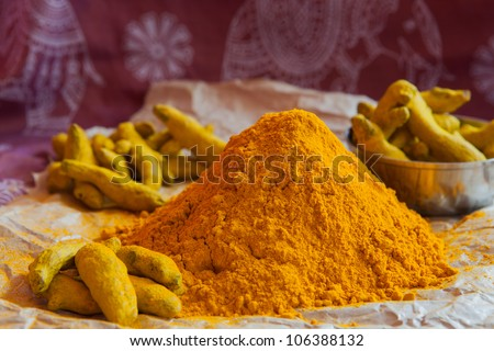 Turmeric powder and sticks on the indian background