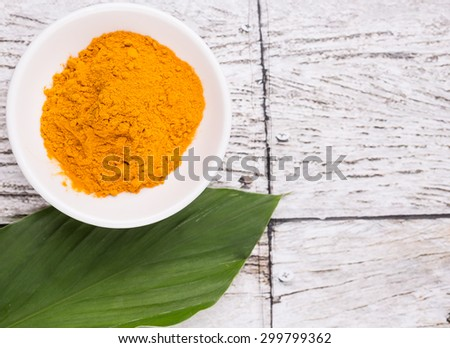 Turmeric powder and turmeric leaves over rustic wooden background - stock photo