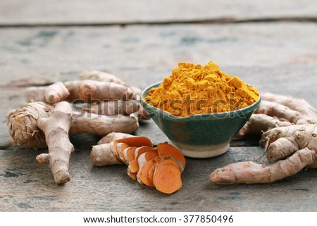 Turmeric powder and turmeric on wooden background. - stock photo