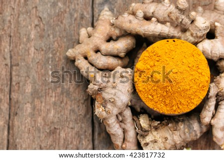 Turmeric powder and turmeric on wooden background.View from the top. - stock photo