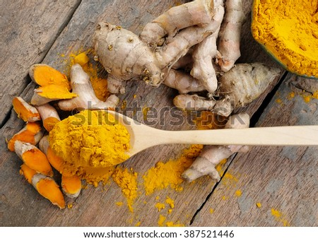 Turmeric powder and turmeric on wooden spoon. - stock photo