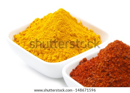 Turmeric Powder, Chilli Powder on White bowl isolated on white background in full-frame.