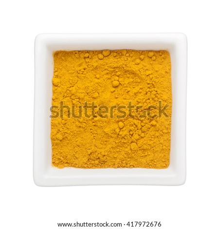 Turmeric powder in a square bowl isolated on white background - stock photo