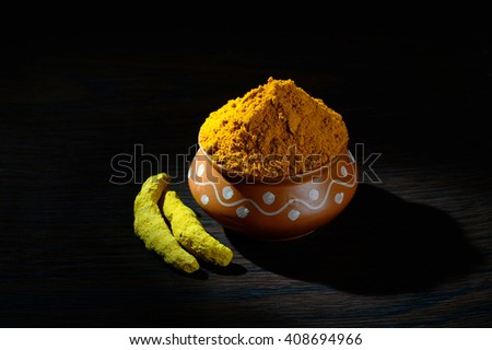 Turmeric powder in clay pot with roots or barks on black background - stock photo
