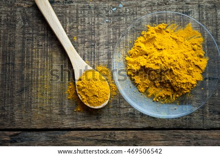 turmeric powder in spoon and roots on wooden table