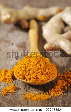 turmeric powder in wooden spoon - stock photo