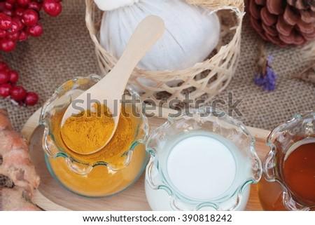 Turmeric powder with honey and milk for scrub - stock photo