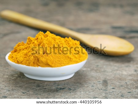 Turmeric powder with wooden spoon on wooden background,with space for text.