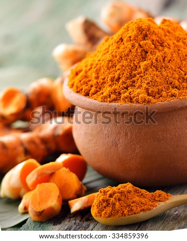 turmeric roots in the basket on wooden table - stock photo