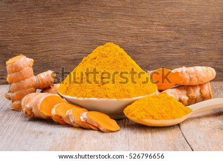 Turmeric roots with turmeric powder on wooden background