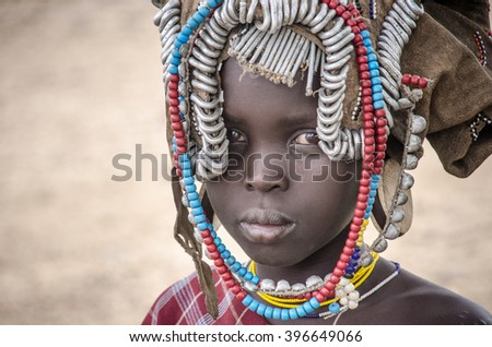 TURMI, ETHIOPIA - AUGUST10, 2014: portrait of young unidentified Mursi tribe girl with typical head decoration. Mursi tribe is endangered because of the construction of the Gibe III dam