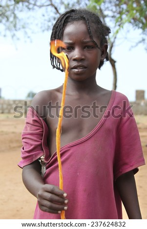 TURMI, ETHIOPIA - NOVEMBER 22, 2011: Portrait of the african girl with the burning candle in hands. November 22, 2011 in Turmi, Ethiopia. - stock photo