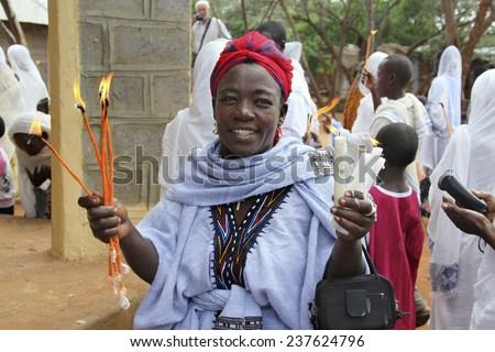 TURMI, ETHIOPIA - NOVEMBER 22, 2011: The woman prays with the burning candles in hands during celebration in orthodox church. November 22, 2011 in Turmi, Ethiopia. - stock photo