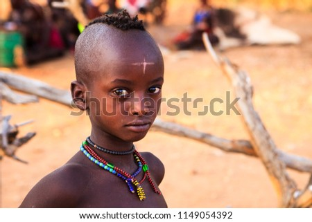 Turmi, Omo River Valley, Ethiopia - January, 2018. Traditional Hamer (Hamar) Village. Boy with a cross-shaped scar on his forehead looking seriously at the camera