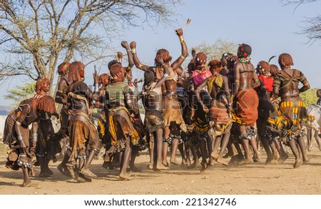 TURMI, OMO VALLEY, ETHIOPIA - DECEMBER 30, 2013: Unidentified group of Hamar women dance at bull jumping ceremony. Jumping of the bull is a rite of passage into manhood for some Omo Valley tribes.  - stock photo
