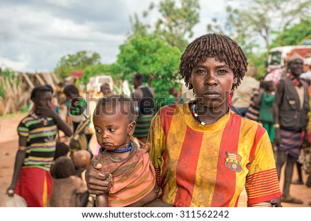 TURMI, OMO VALLEY, ETHIOPIA - MAY 5, 2015: Portrait of a woman from the Hamar tribe with her baby in south Ethiopia. Married hamar women apply red clay to their hair and fashion it into long tufts. - stock photo