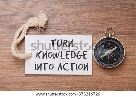 Turn knowledge into action -  Motivation advice handwriting on label with compass - stock photo
