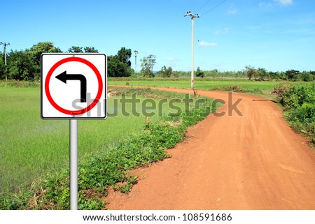 Turn left sign with soil road in countryside