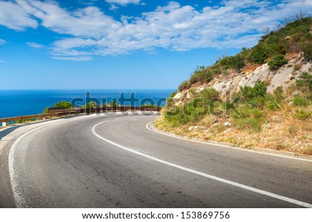 Turn of mountain asphalt road with blue sky and sea on a background - stock photo