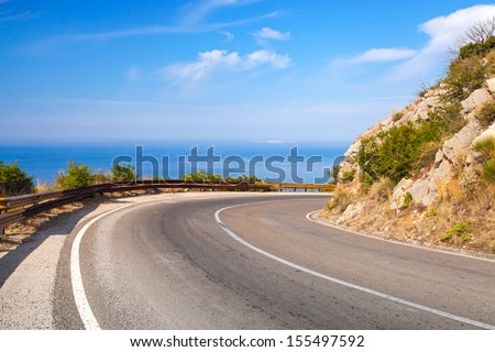 Turn of mountain highway with blue sky and sea on a background - stock photo