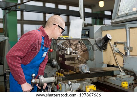 Turner is working on the machine. metal processing. Worker works on a lathe.  Industrial area.
