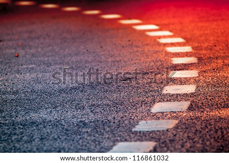 Turning asphalt road with marking lines and bright red reflections - stock photo