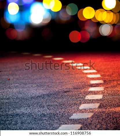 Turning asphalt road with marking lines and reflections with colorful unfocused lights on a background - stock photo