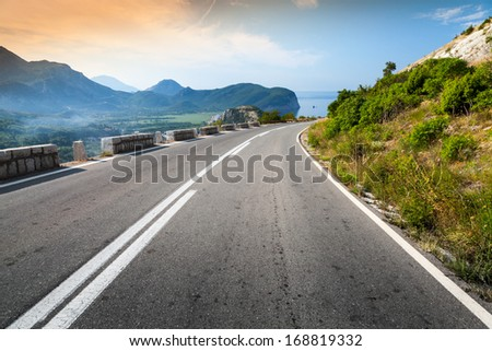 Turning mountain highway with sky and sea on a background - stock photo