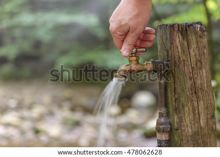 Turning On Or Shutting Off An Outdoor Water Faucet In The Woods.