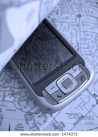 Turning over the page of a street map reveals a Smartphone PDA with GPS capability. The image is in a blue tone. - stock photo