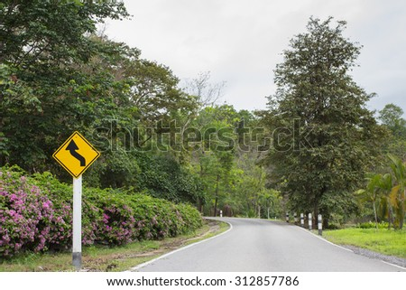 turning yellow traffic sign on road in countryside , nature background - stock photo