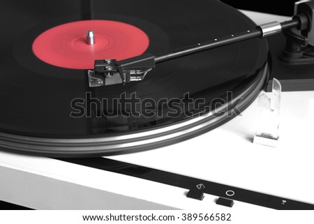 Turntable in yellow case playing a vinyl record with red label. Horizontal photo isolated on black background closeup - stock photo