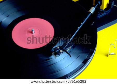 Turntable in yellow case playing a vinyl record with red label. Top view closeup - stock photo