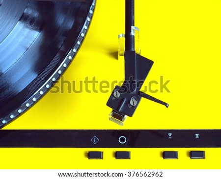 Turntable in yellow case with black tonearm and black control buttons ready for vinyl record playing. Top view closeup - stock photo