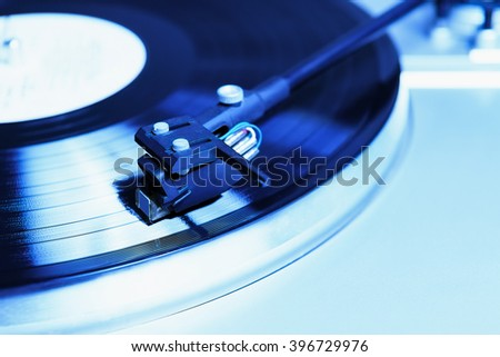 Turntable player with musical vinyl record. Useful for DJ, nightclub and retro theme. Bright blue color - stock photo