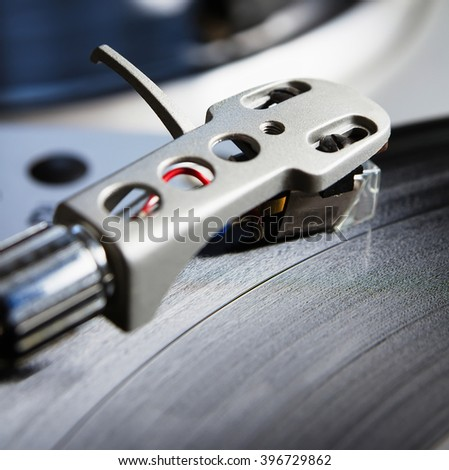 Turntable player with musical vinyl record. Useful for DJ, nightclub and retro theme. Focus on the time code and needle head shell - stock photo