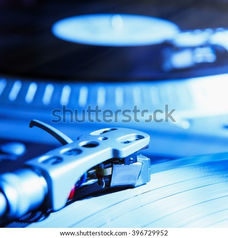 Turntable player with musical vinyl record. Useful for DJ, nightclub and retro theme. Instagram blue filter effect - stock photo