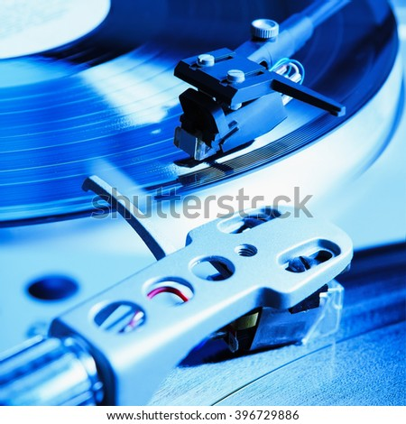 Turntable player with musical vinyl record. Useful for DJ, nightclub and retro theme. Vibrant blue color instagram effect - stock photo