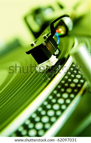 Turntables needle in focus. Vinyl record player playing disc with music. Close up, macro of DJ turntable spinning record. Poster for disc jockey,party or nightclub theme.Analog audio equipment