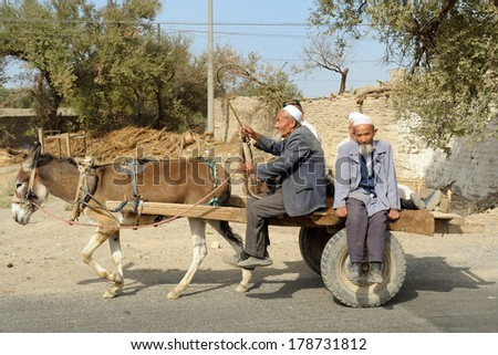 TURPAN, CHINA - OCTOBER 07: Uyghur seniors travel on old cart pulled by donkey on October 07, 2011 in Turpan. - stock photo