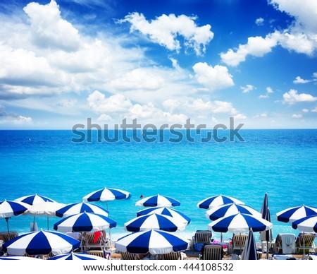 turquiose water of cote dAzur over beach umbrellas under summer sky, France, retro toned - stock photo