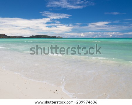 turquoise blue sea with waves and small island far away