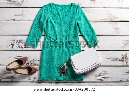 Turquoise dress and white purse. Female outfit on white shelf. Leather clutch purse and dress. Elegant garment and heel shoes. - stock photo
