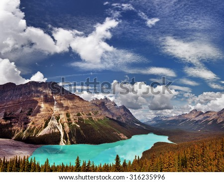Turquoise glacial lake, surrounded by mountains and pine trees - stock photo