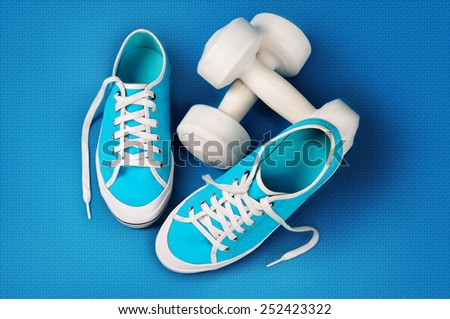 Turquoise gym shoes and white dumbbells on a blue sports mat. - stock photo