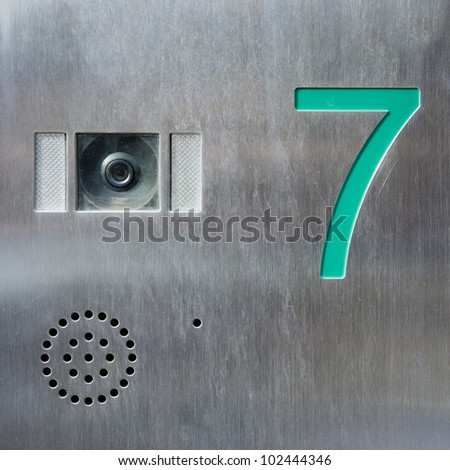 Turquoise house number seven engraved in a stainless steel plate, placed next to an observation camera. - stock photo